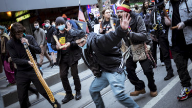 Indigenous protesters do a traditional dance on Bourke Street.