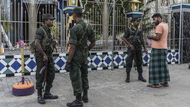 Soldiers stand guard outside the Badhiriy Yah Jum'ah Mosque, in Kattankudy, where Zaharan Hashim worshipped.
