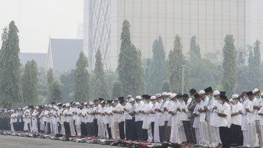 Arms clasped, Muslims pray for rain in Pekanbaru, Riau province, Indonesia.