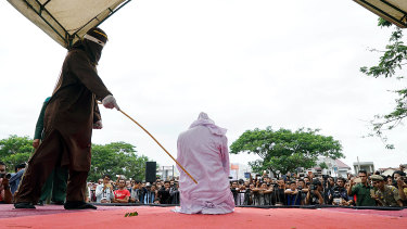 An Acehnese woman being whipped in public for violating sharia law in 2017 for having sex before marriage.