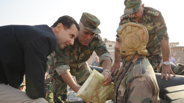Syrian President Bashar al-Assad, left, speaks with Syrian government soldiers during a visit to the strategic town of Habeet, in the north-western province of Idlib, Syria, last week.
