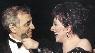 Liza Minnelli welcomes Charles Aznavour onto the stage at the end of her show at the Lido cabaret in Paris in 1987.