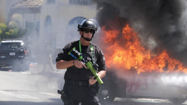 A police officer stands guard while a police vehicle burns in Los Angeles during a protest over the death of George Floyd.