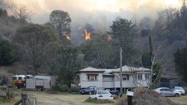 Fire and Emergency crews battle a bushfire near a house in the town of Canungra.