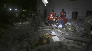 Libyan Red Crescent workers recover migrants bodies after an air strike at a detention centre in Tajoura, east of Tripoli.