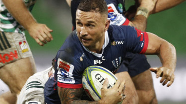 Hard day at the office: Quade Cooper of the Rebels is tackled on Friday night.