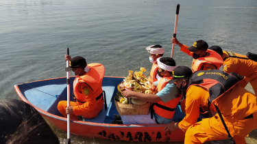 National Search and Rescue Agency personnel help relatives of Captain Gede Kartika, one of the junior officers on the KRI Nanggala, to carry offerings to the sea during a prayer in Celukan Bawang, Bali.