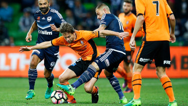 James Troisi of the Melbourne Victory (blue) and Brett Holman of Brisbane Roar (orange) contest the ball during their A-League Semi-Final at AAMI Park on April 30, 2017.
