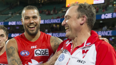 Winners are grinners: Lance Franklin and John Longmire celebrate victory over West Coast on Sunday.