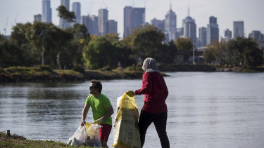 Derek Atkinson and  Farah Rozhan practise plogging along the Maribyrnong River trail at Footscray, with Melbourne CBD in the background.