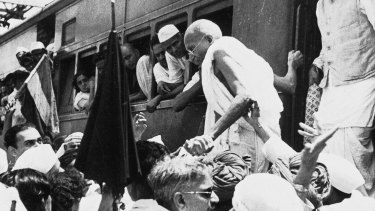 National Congress Party leader Mahatma Gandhi, center, disembarks from a train in Bombay, India on October 5, 1944.