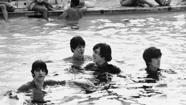 From left: Ringo Starr, Paul McCartney, John Lennon and George Harrison take a dip in the pool in the Bahamas with their clothes on while filming a movie, 1965.