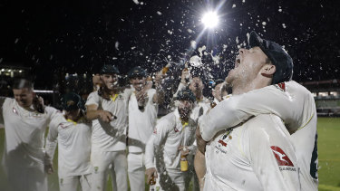 Australian players celebrate retaining the Ashes at Old Trafford.