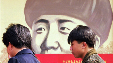 In this 1997 file photo, Chinese wait outside a movie theatre featuring a poster promoting a movie about Feng.