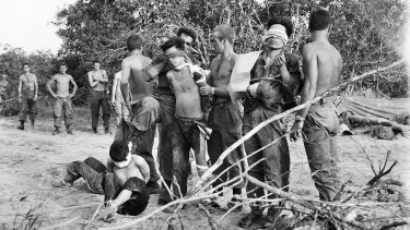Bien Hoa Province, South Vietnam: Blindfolded North Vietnamese soldiers captured on May 28, 1968, await helicopters to take them from the battle area.