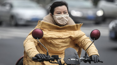 A woman wears a mask in Wuhan, which has been linked to cases of the new coronavirus.