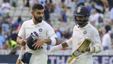 Key partnership: Virat Kohli, left, and Dinesh Karthik leave the field at the end of day three.