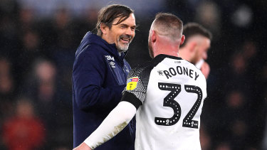 Rooney wearing the controversial No.32 shirt with Phillip Cocu, manager of Derby County.