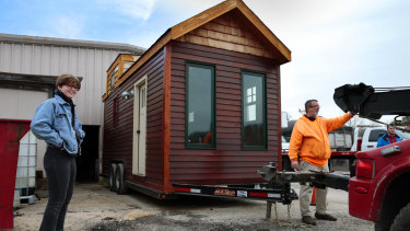 A happy Meghan Panu watches as Mark Ives, owner of Ives Towing, hooks up her recovered tiny house on his Hillsboro lot for its trip home.