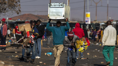 Looters carry items at Letsoho Shopping Centre in Katlehong, east of Johannesburg, South Africa.