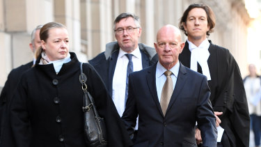 Clifford John Gerathy (second from right) leaves the Supreme Court in Melbourne on Friday.