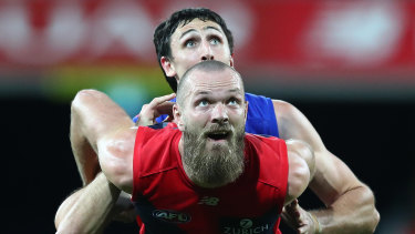 Eyes on the prize: Max Gawn gets front spot in a ruck contest against Oscar McInerney of the Lions.