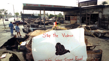 In this May 3, 1992 file photo, a cross, flowers and a banner urging an end to violence adorn the ruins of a service station at Florence and Normandie Avenues in South-Central Los Angeles.