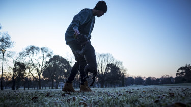 Chris Davenport and Britney the pup play in a frosty Princes Park, Carlton, on Monday morning.
