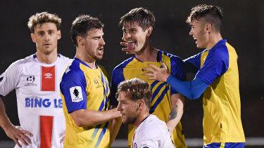 Matt Richardson celebrates with Brisbane Strikers teammates after scoring the winning goal against Manly United.