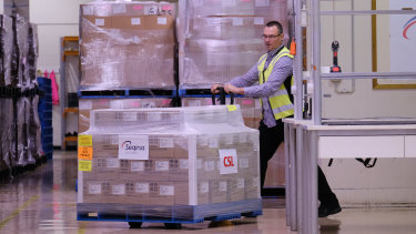 A worker rolls a batch of AstraZeneca vaccines onto a truck at a CSL factory in Melbourne.