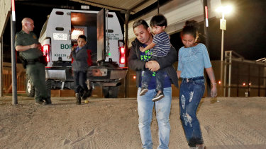 A Honduran man carries his three-year-old son as his daughter and other son follow to a transport vehicle after being detained by US Customs and Border Patrol agents in San Luis, Arizona.