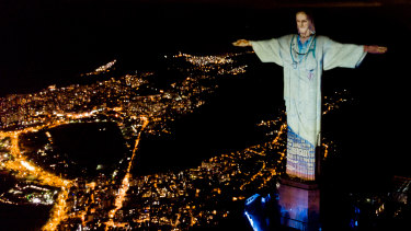 """Illuminated statue of Christ the Redeemer that reads """"Thank you"""" as Archbishop of the city of Rio de Janeiro Dom Orani Tempesta performs Mass on Easter Sunday."""