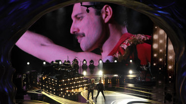 An image of Freddie Mercury appears on screen as Brian May, left, and Adam Lambert of Queen perform at the Oscars.