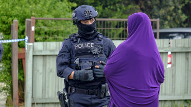 A police officer speaks to a woman who arrived at the Werribee home of Shire Ali's parents on Saturday.