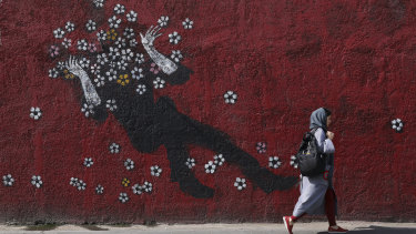 A woman walks past a mural in downtown Tehran, Iran, on Sunday.