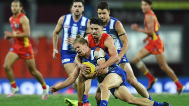 Block and tackle: North Melbourne's Jed Anderson is brought down by Gold Coast's rising star Izak Rankine.
