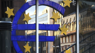 A Euro sign sculpture is reflected in a building near the European Central Bank (ECB) headquarters in Frankfurt, Germany.