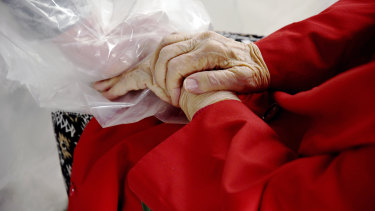 """Gregg MacDonald holds hands with his 84-year-old mother, Chloe MacDonald, at the """"hug tent""""."""