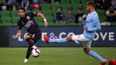 Through ball: Newcastle's Daniel Georgievski hits a pass under pressure from City's Dario Vidosic.