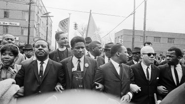 Martin Luther King jnr, fourth from left, foreground, locks arms with his aides as he leads a march of several thousand to the courthouse in Montgomery, Alabama. From left are: an unidentified woman, Reverend Ralph Abernathy, James Foreman, King, Jesse Douglas snr and John Lewis.