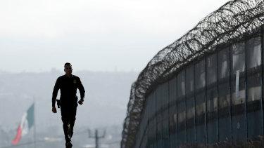 Border Patrol agent Eduardo Olmos walks near the secondary fence separating Tijuana, Mexico, background, and San Diego in San Diego, California.