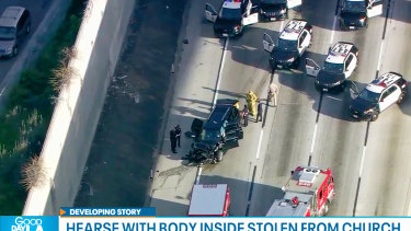 Los Angeles police officers at the scene of the end of a pursuit of a hearse with a body inside in South Los Angeles.