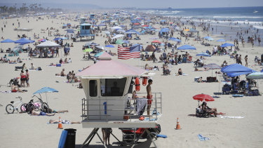 A lifeguard keeps watch over a packed beach in Huntington Beach on Monday.