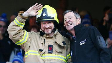 Nathan Buckley wearing Murray Swinton's uniform alongside Neale Daniher in 2018.