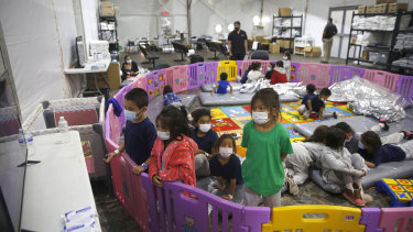 Young unaccompanied migrants, from ages 3 to 9, watch television inside a playpen at the US Customs and Border Protection facility in the Rio Grande Valley, in Donna, Texas.