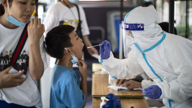 A medical worker takes samples during a mass COVID-19 test in a residential block of Wuhan.