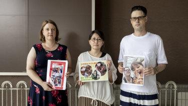Catherine Henderson, Izumi Dobashi and Scott McIntyre hold photos up of their children.