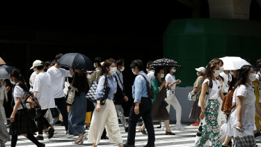 Pedestrians wearing protective face masks cross the road at Umeda district in Osaka.