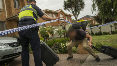 Members of Victoria Police enter  the crime scene at Mill Park.