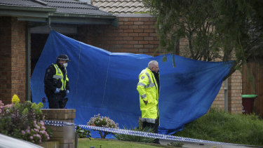 A tarp covered the garage and roller door at the front of the property in Cranbourne North after a 36-year-old woman was found dead.